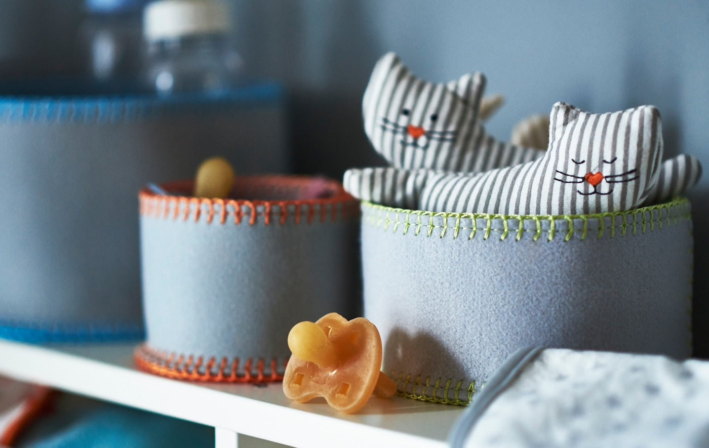 A close-up of felt storage baskets holding baby stuff like dummies and cat-shaped rattles.