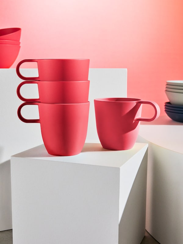 A close-up of four TALRIKA mugs in bright red — made in light-weight, plant-based plastic.
