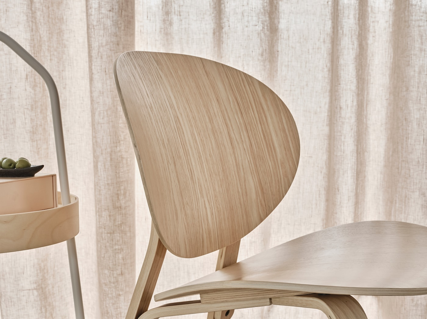 A close-up of FRÖSET easy chair in white stained oak veneer made in a Scandinavian design with clean lines.