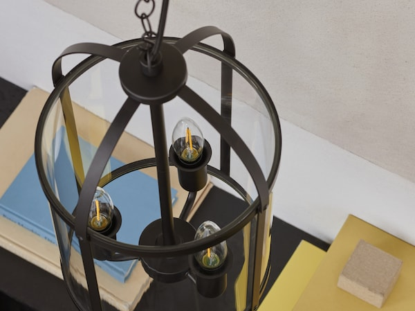 A close-up of GALJON pendant lamp made in a lantern design holding three deco bulbs with colourful books in the background.