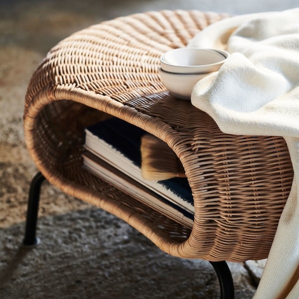 A close-up of GAMLEHULT footstool with tightly woven natural rattan and mouth-like opening with magazines inside.
