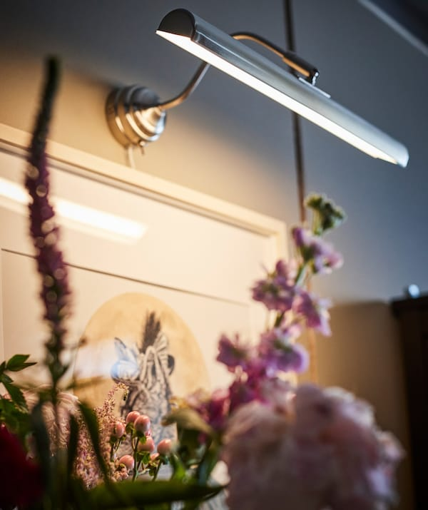 A close up of IKEA ÅRSTID picture light above a flower arrangement.