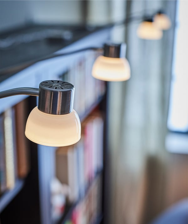 A close-up of IKEA LINDSHULT LED cabinet lights illuminating books in a bookcase.