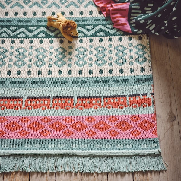 A close-up of KÄPPHÄST rug with a pattern inspired by traditional Swedish mittens in green, red, and pink.