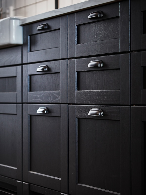 A close-up of kitchen cabinets with LERHYTTAN drawer fronts in stained black fitted with ENERYDA cup handles.