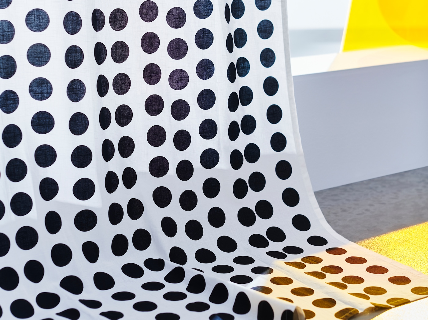 A close-up of KLARASTINA curtains with a pattern of black polka dots on a white background.