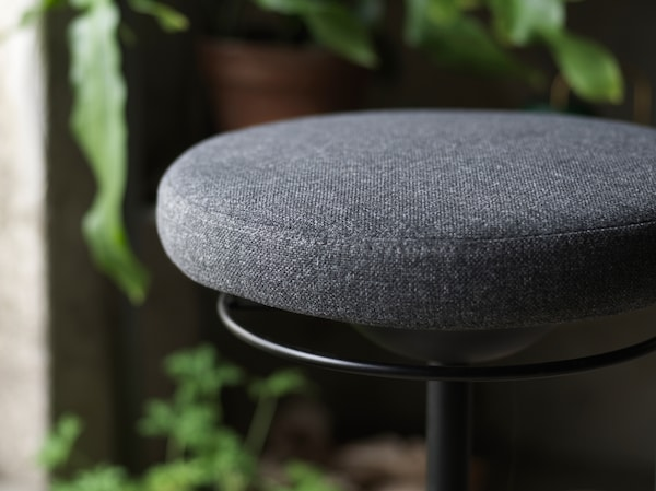 A close-up of LIDKULLEN active sit/stand support with a focus on its rounded padded seat in dark gray.