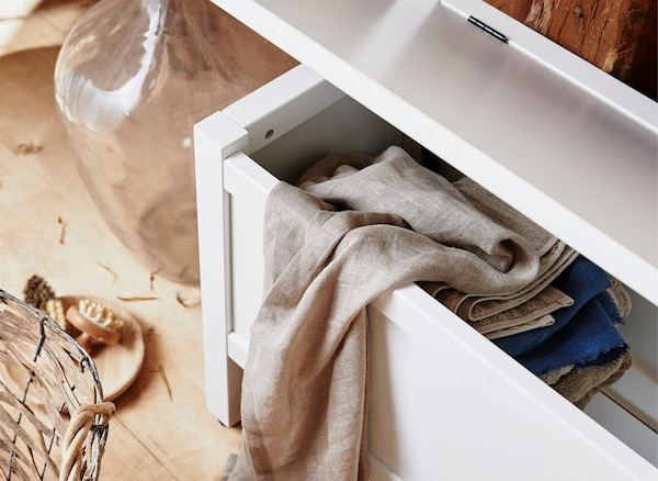 A close-up of linens and towels in a storage compartment inside a bench.