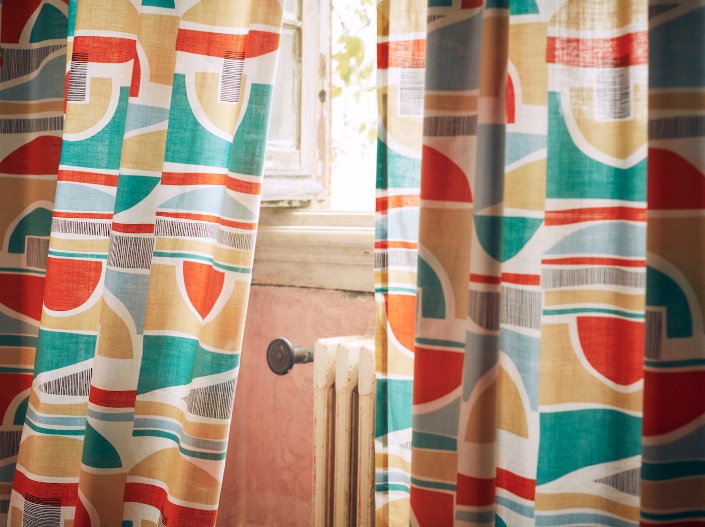 A close-up of MARTORN curtains with a multi-coloured graphic pattern that looks like it could be taken from the 1960s.
