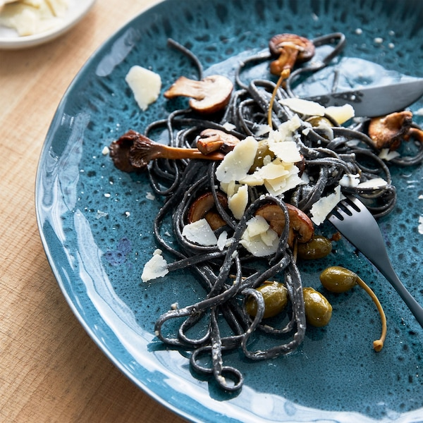 A close-up of mushrooms and black pasta on a blue IKEA ERTAPPAD dish that's glazed to create unique patterns of random circles.