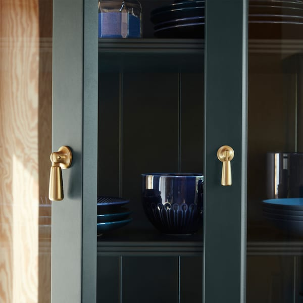 A close-up of open LOMMARP cabinet with glass doors in dark blue-green with a golden drop handle.