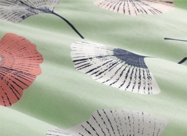 A close-up of pale green fabric with flower pattern.