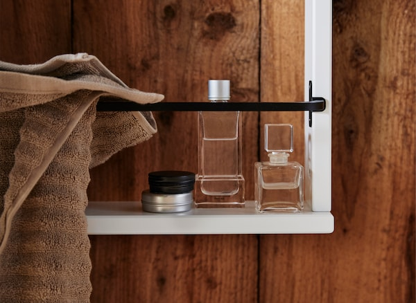 A close-up of perfume bottles on a white wall shelf with a towel hanging on a black rail, on a wooden wall.