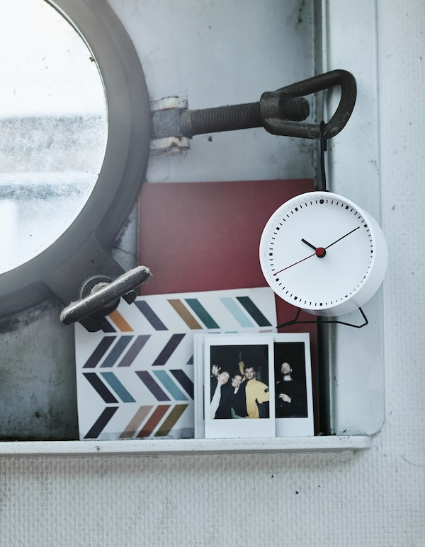 A close-up of pictures and an alarm clock on a small shelf next to a porthole window.