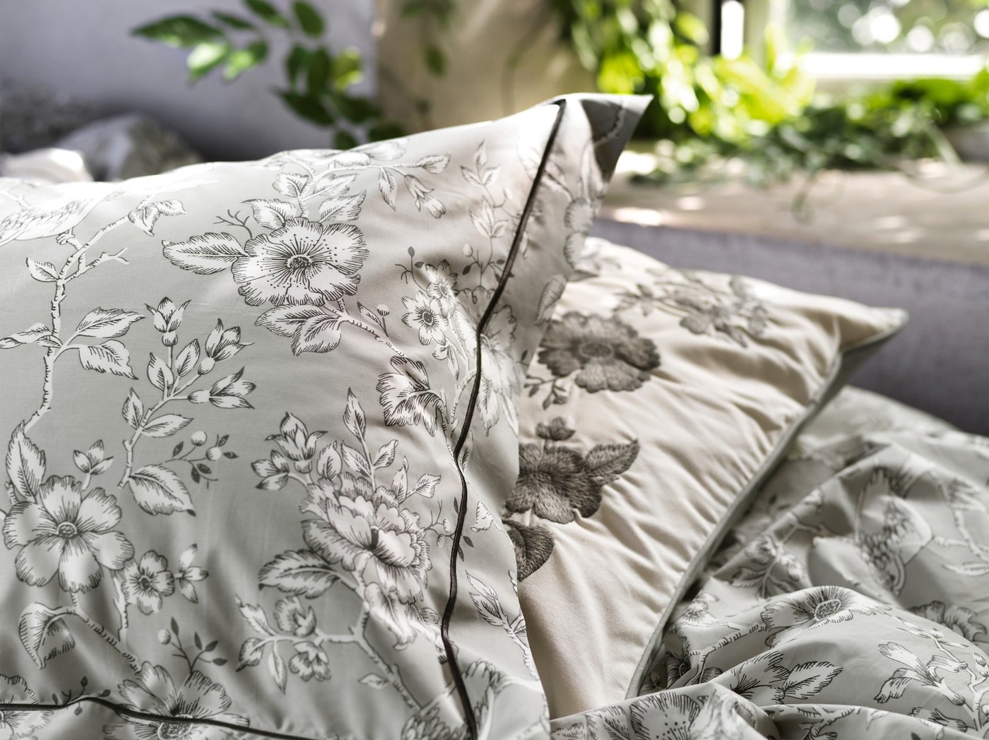A close-up of PRAKTBRÄCKA quilt cover and pillowcase in gray featuring traditional floral patterns in black and white.