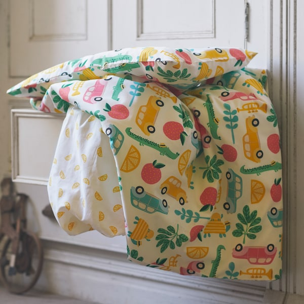 A close-up of RÖRANDE quilt cover and pillowcase with a colourful graphic print, placed on top of a pulled-out drawer.