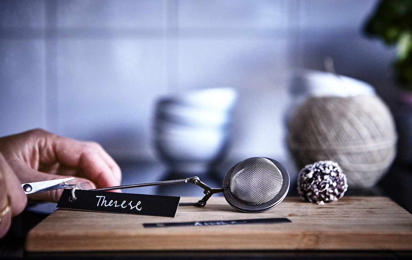 A close-up of someone tying a name tag onto an IKEA IDEALISK tea infuser.