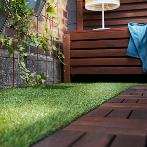 A close up of the faux grass and wooden outdoor decking in an outdoor setting.