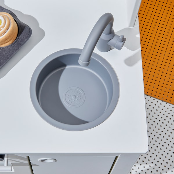 A close-up of the grey sink and kitchen tap of the white SPISIG play kitchen with curtains.