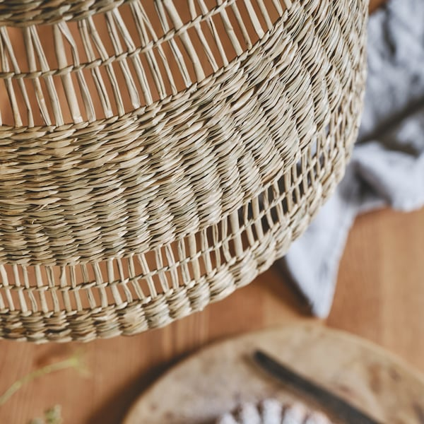 A close-up of the handwoven TORARED pendant lampshade, made in seagrass with natural colour variations.