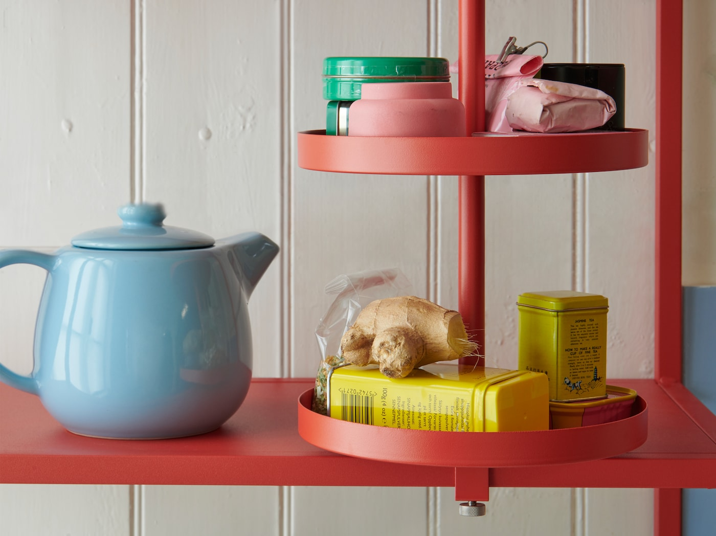A close-up of the red-orange ENHET swivel shelf for the kitchen holding different tins and packages, as well as some ginger.
