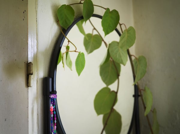 A close-up of the round mirror of the black KORNSJÖ cabinet with the vine of a plant climbing up its side.