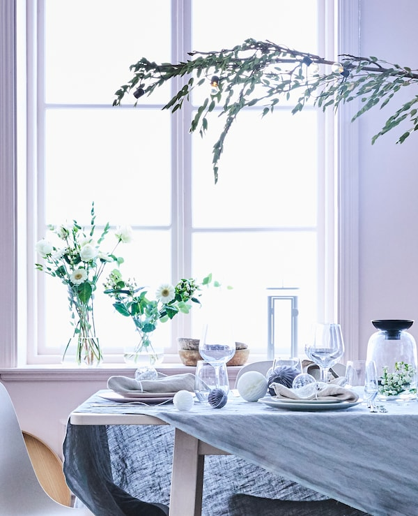 A close-up of the set dining table with glassware and decorations in white and grey together with a grey linen tablecloth.