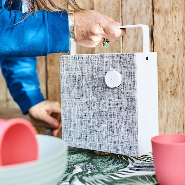 A close up of the white and grey ENEBY bluetooth speaker being lifted by a person.