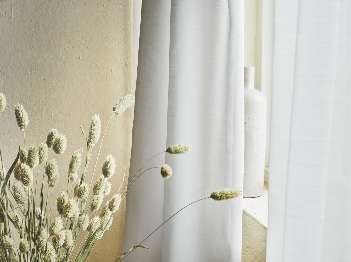 A close-up of the white GUNRID air purifying curtains hanging by a window next to dried wheat stalks.