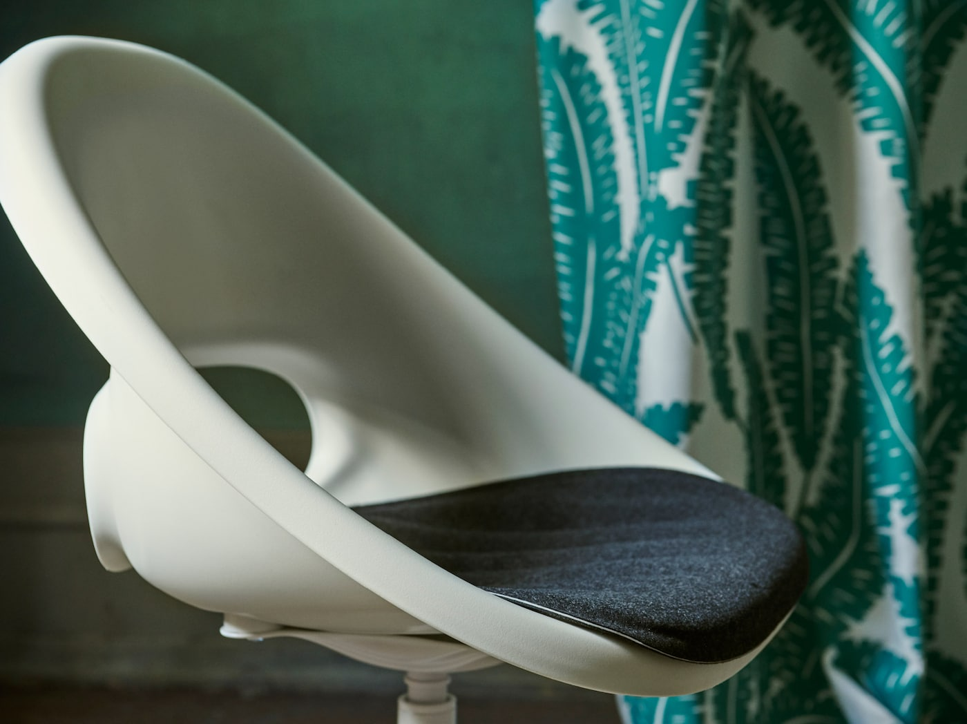 A close-up of the white LOBERGET/BLYSKÄR swivel chair with a rounded retro design placed in a green room.