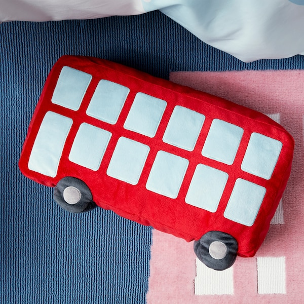 A close-up of UPPTÅG cushion in the shape of a red bus and made of recycled polyester that's soft on the cheek.