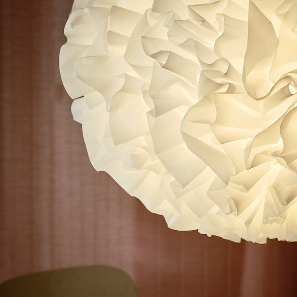 A close-up of VINDKAST pendant lamp made with fluffy white ruffles in a pompom shape with a pink curtain in the background.
