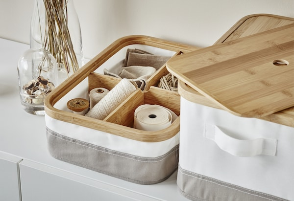 A close-up of white and grey IKEA storage boxes with wooden lids and sewing items stored in wooden compartments inside.