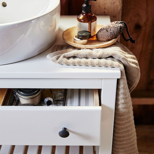 A close-up of white-stained pine HEMNES open bathroom vanity with one drawer.