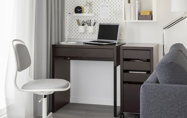 A close up on a desk with laptop, peg board and swivel chair.