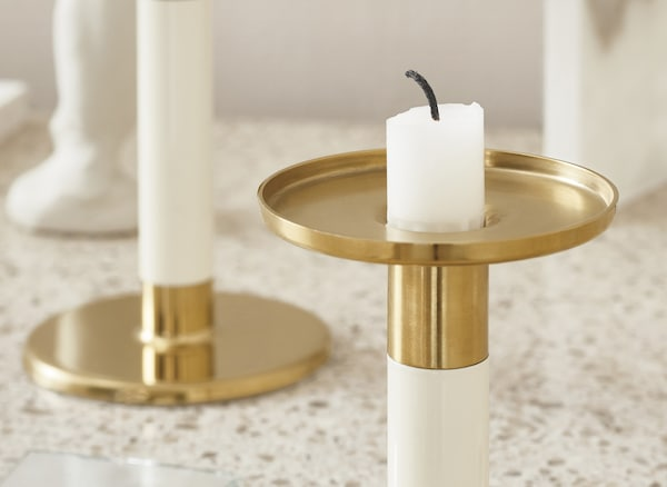 A close-up on an ivory and gold-coloured candlestick.