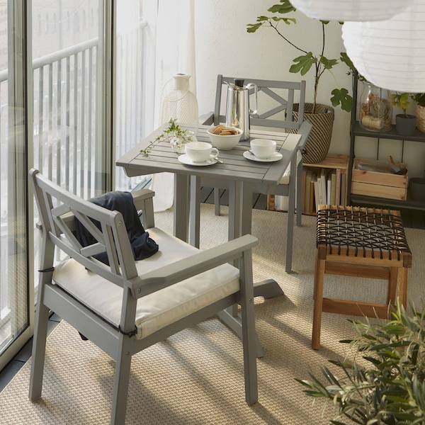 A closed balcony with a table and two chairs with armrests in grey, an outdoor stool, white pendant lamps and a beige rug.