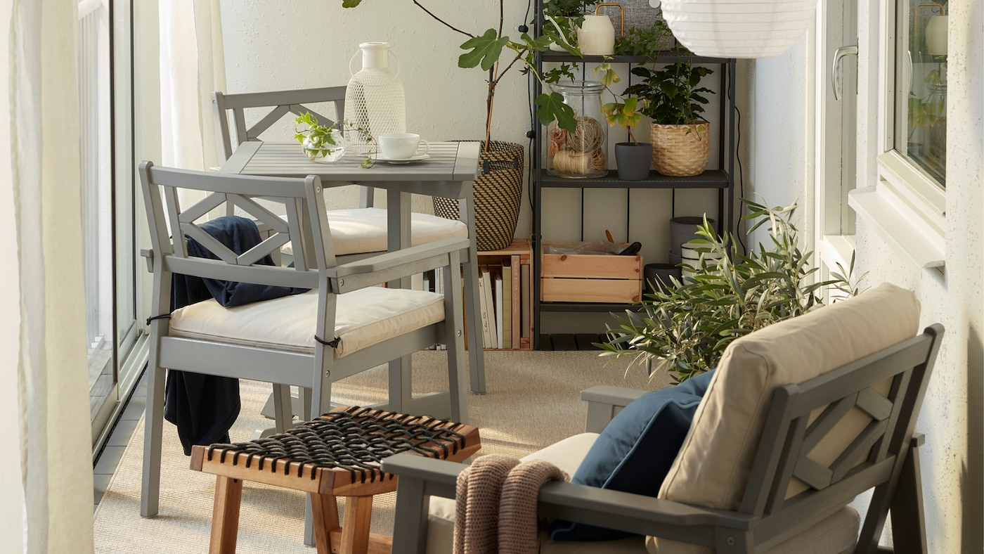 A closed balcony with grey BONDHOLMEN furniture, round pendant lamp, a beige rug, white curtains and lots of plants.