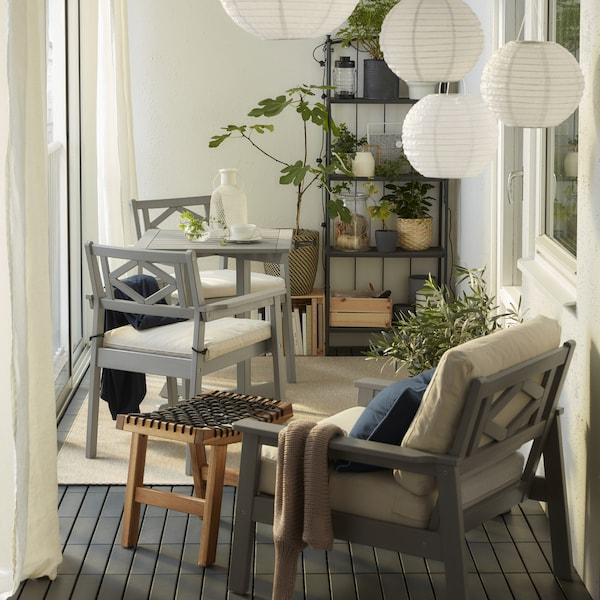 A closed balcony with grey BONDHOLMEN furniture, round pendant lamps, a beige rug, white curtains and many green plants.