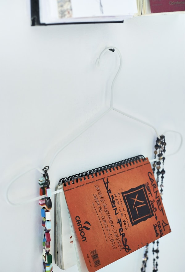 A closeup of a notebook and jewellery being displayed on a slim white clothes hanger.