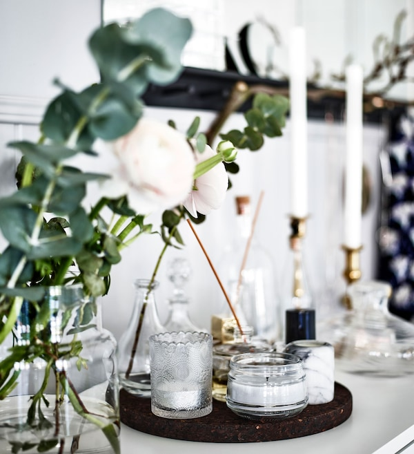 A closeup of a scent station with candles, flowers and perfumes set on circular trays or clear glass vases.