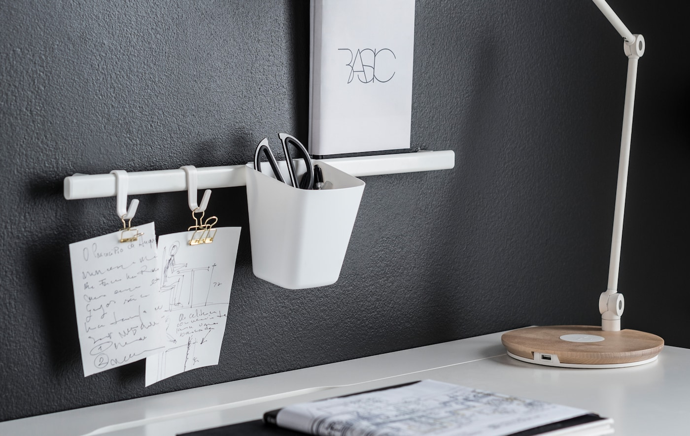 A closeup of a small white rail mounted to a wall, holding a few clipped notes and white cup holder on white hooks.