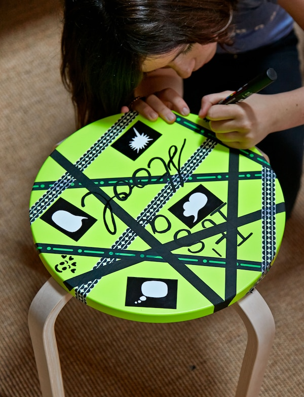A closeup of a stool's seat painted lime green and being decorated with black deco tape and handwritten words.