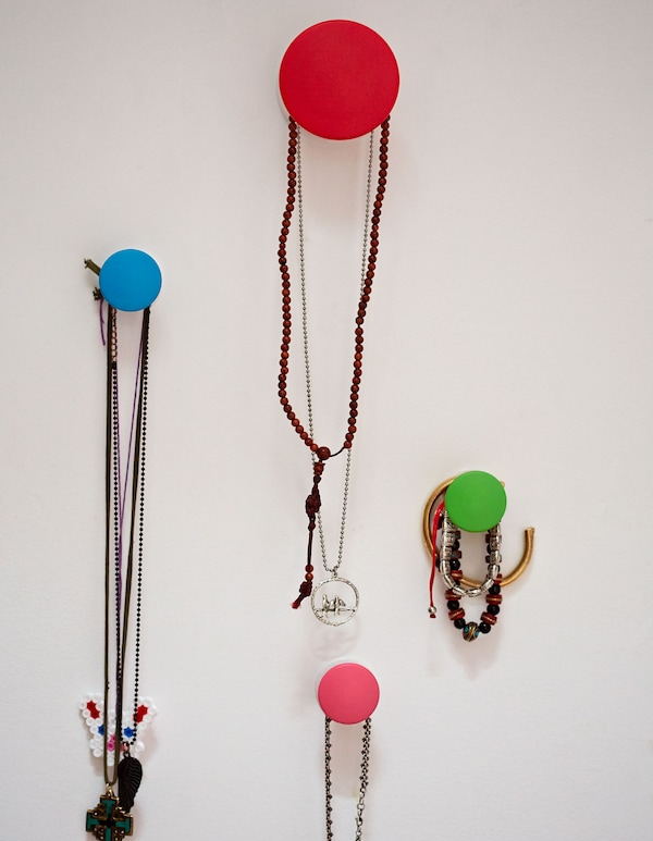 A closeup of colourful IKEA circlular chooks mounted to a white wall, hanging a collection of necklaces and bracelets.