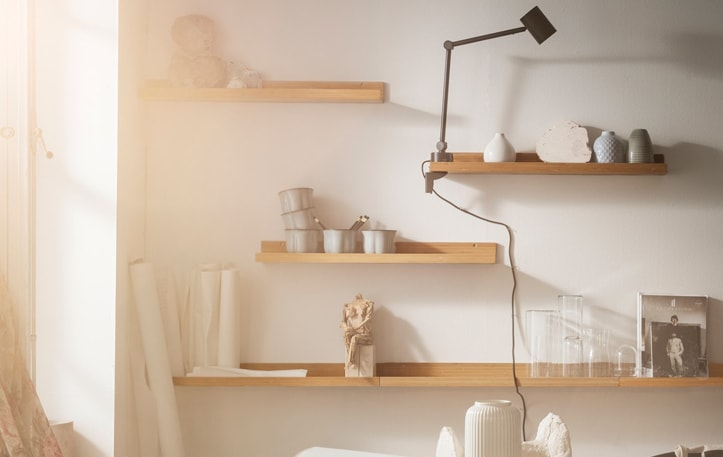 A closeup of four shelves on a wall with decorations, a light and art supplies on the shelves.