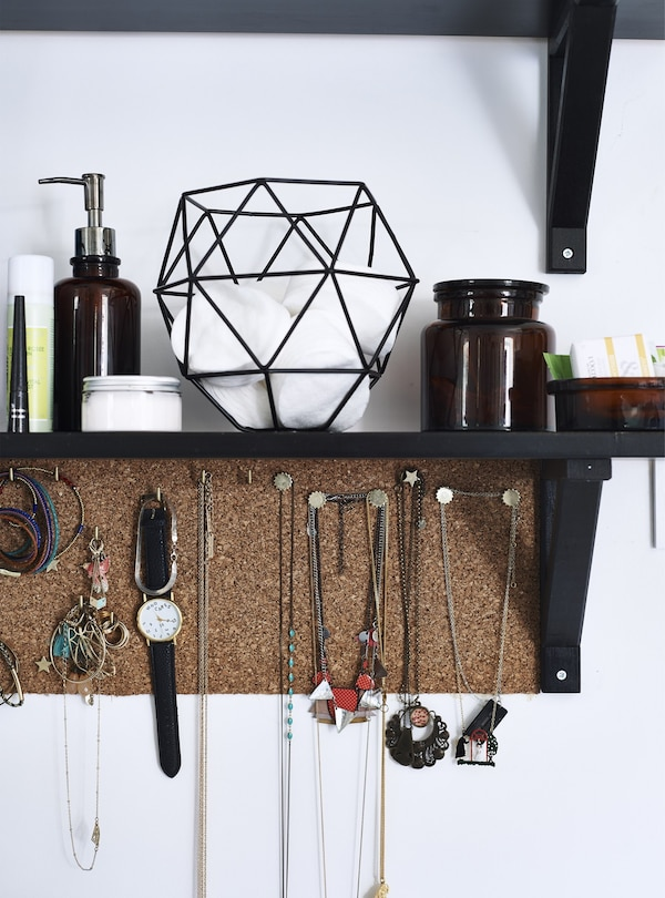 A closeup of jewellery hanging from a cork board below a black shelf.