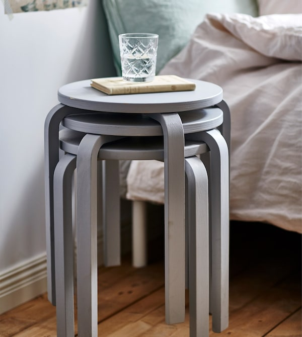 A closeup of three stacked grey stools being used as a bedside table.