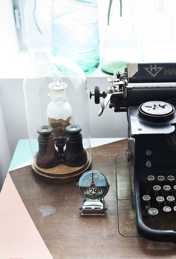 A closeup of tiny binoculars kept safely in an oval-shaped glass display case, next to a vintage typewriter.