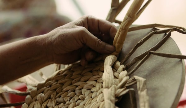 A closeup showing how aristan women expertly hand-weave an IKEA SOARÉ round place mat on a rounded surface.