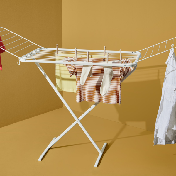 A clothes rack on an ochre-yellow background.